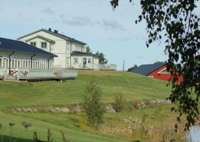 Två ljust grågröna hus i en liten sluttning, med ett rött hus i bakgrunden.