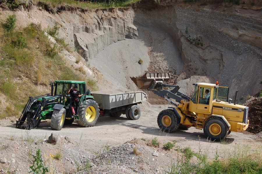 En gul lastmaskin är på väg att tömma skopan på ett släp som står bakom en grön traktor.