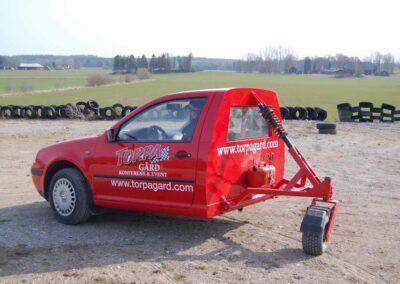 En röd, halv bil, med två hjul fram och ett kundvagnsliknande hjul bak.