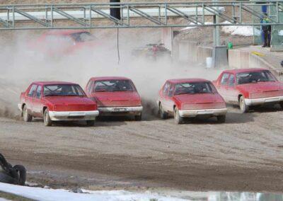 Fyra röda folkrace-bilar kör iväg från starten, det har bildats ett damm-moln bakom dem.