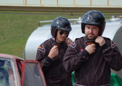 Två män står vid en folkrace-bil och knäpper sina hjälmar.