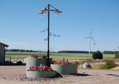 En lyktstolpe med planteringar runt omkring, i bakgrunden finns ett vindkraftverk.