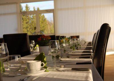 Ett bord dukat för fest, med gröna servetter och vinglas.