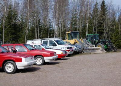 Fem bilar, en lastmaskin och en traktor står parkerade bredvid varandra.