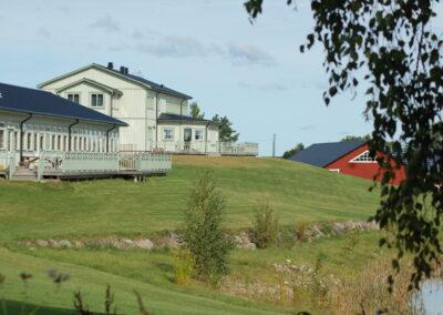 Två ljust grågröna hus på en liten kulle, med ett rött hus i bakgrunden.