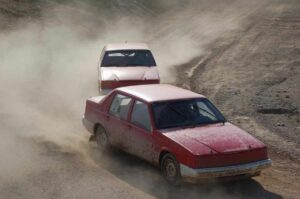 Två röda folkrace-bilar efter varandra.