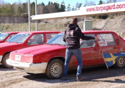 En man med flagga skickar iväg den första av 3 folkrace-bilar.