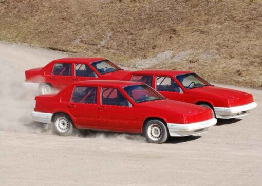 Tre röda folkracebilar kör nästan jämsides på en grusbana, det dammar lite runt hjulen.