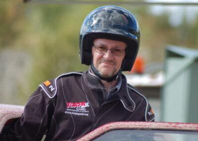 En glad man med hjälm kliver ur en folkracebil.