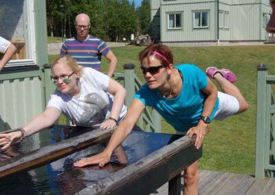 Två kvinnor står framåtlutade över ett bord med vatten på, den ena kvinnan har ett ben i luften. En man står och tittar på.