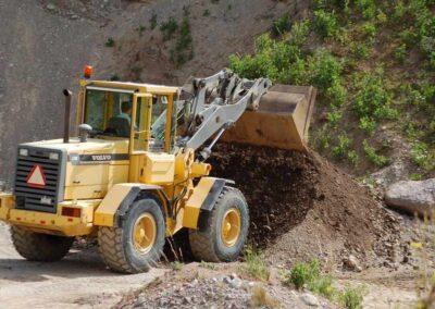 En gul lastmaskin tömmer skopan på jord