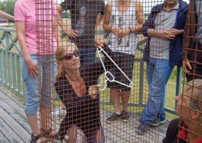 En kvinna lyfter en galge från golvet och upp över ett armeringsnät, med fingrarna genom nätet. Flera personer tittar på.
