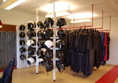 Ett stort antal hjälmar hänger på två stolpar. Bakom dem hänger tre rader med overaller.