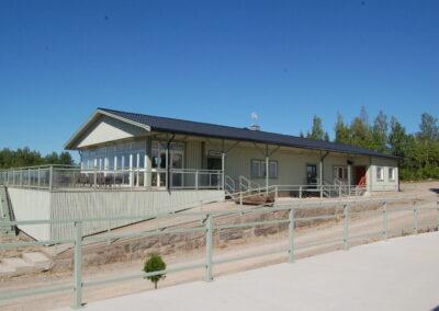 Ett ljust grågrönt hus med blå himmel och träd bakom. Huset har tre ingångar, stora fönster och en altan.