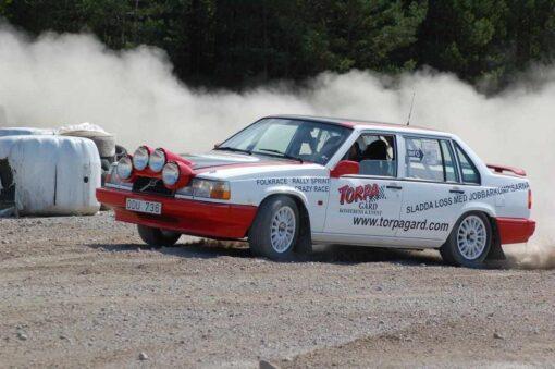 En vit/röd rallybil med ett stort damm-moln bakom. På sidan av bilen finns en stor logga och text.