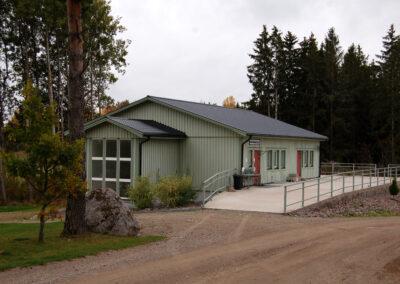 Ett grågrönt hus med två röda dörrar, ett stort fönster på gaveln och en stor altan.