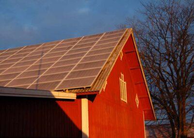 En röd förrådsbyggnad med plåttak, hela taket är täckt av solpaneler.