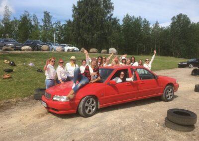 Ett möhippegäng samlade runt en av Torpa Gårds Crazy race-bilar, en Volvo med två fronter