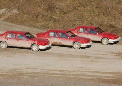 Tre röda, smutsiga folkrace-bilar ligger nästan jämsides på en grus-motorbana.